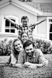 Счастливая семья лежа поверх одина другого во дворе стоковые изображения