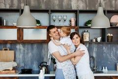Счастливая семья - мама, папа и сын в кухне дома в утре стоковое фото rf