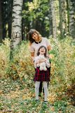 Счастливая семья мамы и дочери обнимая и смеясь над осенью Стоковые Изображения RF