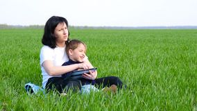 Счастливая семья: мать и ребенок сидя на зеленой траве Притяжка мамы и мальчика с планшетом Технология, применения акции видеоматериалы