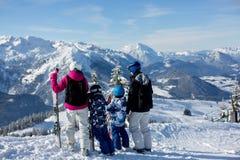 Счастливая семья, мать, отец и 2 дет, катаясь на лыжах Стоковое Изображение
