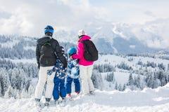Счастливая семья, мать, отец и 2 дет, катаясь на лыжах Стоковое Изображение RF