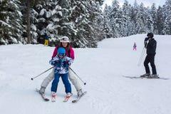 Счастливая семья, мать, отец и 2 дет, катаясь на лыжах Стоковая Фотография