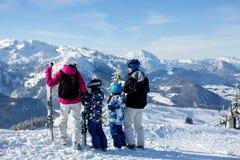 Счастливая семья, мать, отец и 2 дет, катаясь на лыжах Стоковая Фотография RF