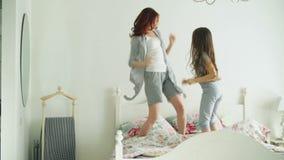 Счастливая семья милой дочери и молодой матери скача и танцуя на кровати пока имейте потеху во время утра на праздниках на сток-видео