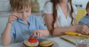 Счастливая семья молодая красивая мать в белом платье с 2 сыновьями в голубых рубашках подготавливая белую кухню видеоматериал
