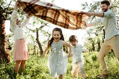 Счастливая семья наслаждаясь весной совместно на яблоневом саде стоковые изображения