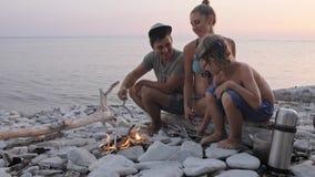 Счастливая семья наслаждаясь заходом солнца лета на диком пляже вокруг костра акции видеоматериалы