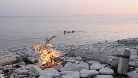 Счастливая семья наслаждаясь заходом солнца лета на диком пляже вокруг костра видеоматериал