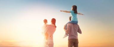 Счастливая семья на заходе солнца стоковое изображение