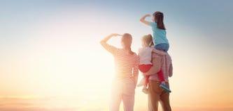 Счастливая семья на заходе солнца стоковая фотография rf