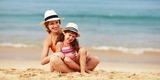 Счастливая семья на пляже объятие дочери матери и ребенка на море стоковое изображение
