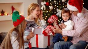 Счастливая семья на подарках отверстия рождества совместно Стоковая Фотография