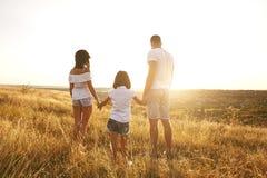 Счастливая семья на природе летом на заходе солнца стоковые изображения rf