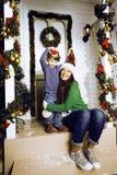 Счастливая семья на рождестве в красных шляпах ждать gests и усмехаться внешние Стоковое Фото
