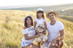 Счастливая семья на outdoors пикника на заходе солнца стоковая фотография rf