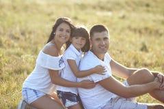 Счастливая семья на outdoors пикника на заходе солнца стоковое изображение