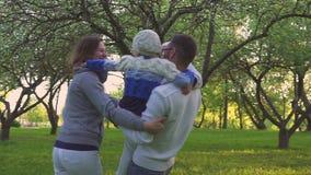 Счастливая семья обнимая на траве Родители и их 2 дочери обнимают на лужайке парка Цветя сад видеоматериал