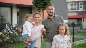 Счастливая семья около их нового дома r Они имеют много потеху совместно сток-видео