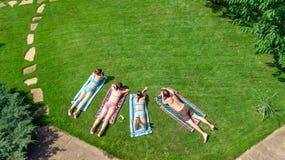 Счастливая семья ослабляя бассейном, воздушный взгляд трутня сверху родителей и дети имеют потеху на каникулах, выходных семьи стоковые изображения
