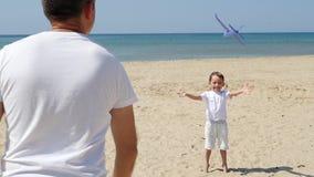 Счастливая семья: отец и сын играя морем Человек запускает самолет игрушки Перемещение и внешнее воссоздание видеоматериал