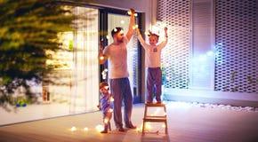Счастливая семья, отец с сыновьями украшает wi района патио открытого пространства стоковая фотография rf