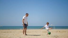 Счастливая семья: папа и его сын играя с футбольным мячом на песочном береге моря, в замедленном движении акции видеоматериалы