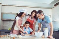 Счастливая семья подготавливает выпечку в кухне стоковые изображения rf
