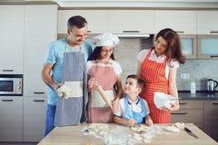Счастливая семья подготавливает выпечку в кухне стоковое фото
