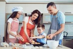 Счастливая семья подготавливает выпечку в кухне стоковое фото rf