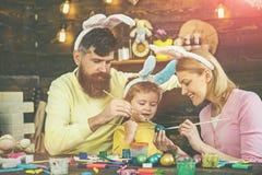 Счастливая семья подготавливая для пасхи стоковые изображения