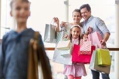 Счастливая семья показывает их хозяйственные сумки стоковое фото rf
