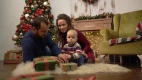 Счастливая семья празднуя мать рождества совместно, отца и маленький младенца сидя на поле в комнате с сток-видео