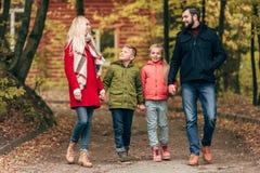 счастливая семья при 2 дет держа руки и идти Стоковые Изображения RF