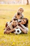 Счастливая семья при 2 дет лежа в куче на траве Стоковое фото RF