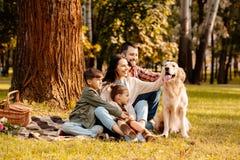 Счастливая семья при 2 дет сидя на одеяле пикника и petting Стоковые Изображения RF