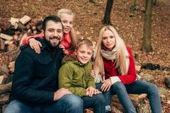 счастливая семья при 2 дет сидя совместно и усмехаясь на камере Стоковые Изображения