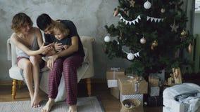 Счастливая семья при милая маленькая дочь сидя около рождественской елки и используя smartphone дома Стоковые Фото