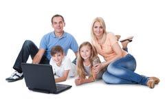 Счастливая семья при 2 дет используя компьтер-книжку Стоковая Фотография RF