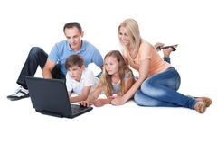 Счастливая семья при 2 дет используя компьтер-книжку Стоковое Изображение