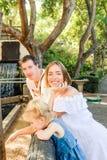 Счастливая семья - родители при ребенок девушки малыша имея потеху в зоопарке Воссоздание семьи, тратя концепцию времени совместн Стоковые Изображения