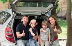 Счастливая семья сидя в хоботе автомобиля и показывая большие пальцы руки вверх стоковые изображения
