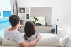 Счастливая семья смотрит телевидение на выходных стоковая фотография