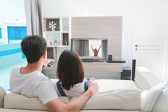 Счастливая семья смотрит телевидение пока сидящ на софе в Стоковое Фото