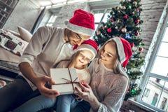 Счастливая семья смотря внутри волшебной подарочной коробки рождества стоковое фото
