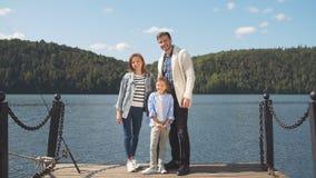 Счастливая семья смотря камеру пока представляющ на пристани на тихом озере видеоматериал