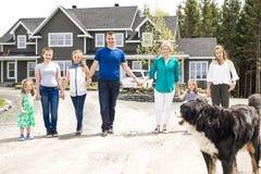Счастливая семья стоя перед домом Стоковые Фотографии RF