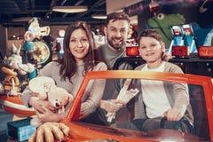 Счастливая семья, сын сидя на автомобиле игрушки стоковое изображение