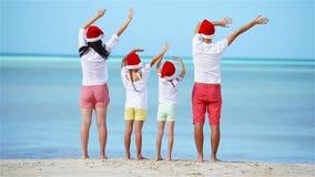 Счастливая семья с 2 детьми в шляпе Санты на летних каникулах акции видеоматериалы