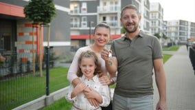 Счастливая семья с детьми стоя на открытом воздухе держа ключи большого загородного дома Усмехаясь роскошные владельцы недвижимос сток-видео